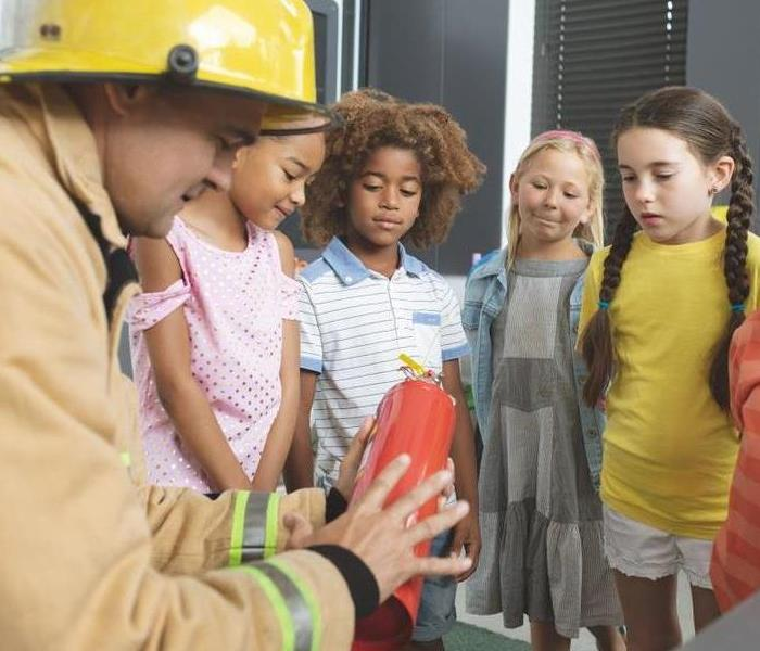 a firefighter showing kids a fire extinguisher
